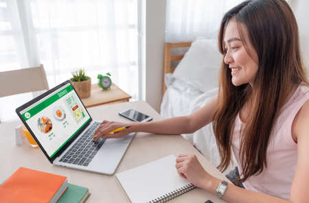 Asian woman order grocery online with laptop at home.new normal digital lifestyle with technology shopping onlne