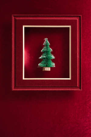 Merry Christmas and happy new year text and Christmas tree in felt photo frame on velvet red felt fabric  top view background Stock Photo