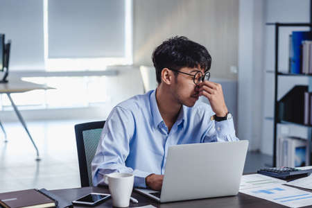 asian businessman get stress and headache when working with laptop on desk at modern office.business fail concept.man caught eye when overworked. Stock Photo