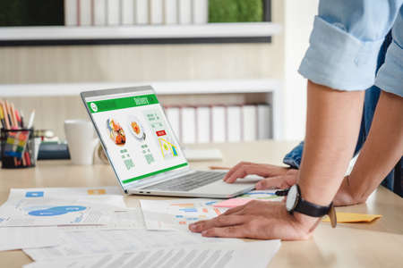 close up hand creative designer team order food online while meeting break for lunch on desk with paperwrok on laptop in meeting room at modern office Stock Photo