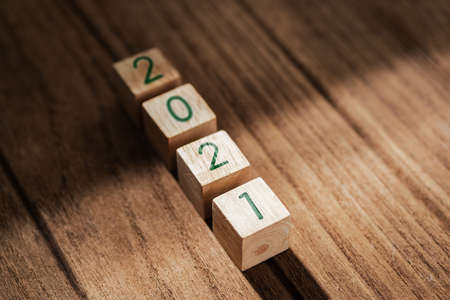 2021 happy new year on wood block on wood table and concrete wall with sunlight from window.hope new year concept