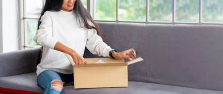 asian woman satisfied and smile unpack parcel on sofa at home.recieve goods delivery from online purchase store.online shopping omni channel post mail shipping concept