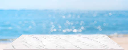summer background.Empty perspective marble table with blur sea and sky bokeh background, banner mockup template for display of product Stock Photo