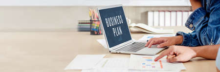 close up hand creative designer team casual meeting and brainstorming business plan with paperwork and online data on laptop in meeting room at modern office