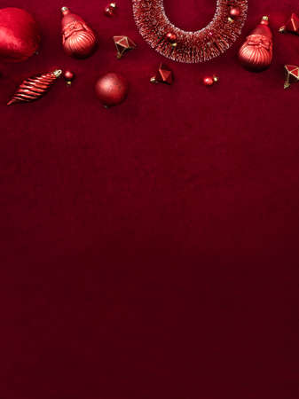 red christmas decoration bauble and ribbon on velvet red felt fabric  top view table backgorund.vertical layout