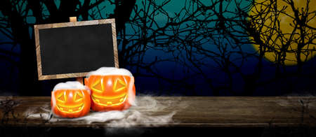 Halloween background.Pumpkin with smoke on grunge blackboard on wood table at spooky dead tree and full moon in blue gradient night sky,Halloween invitation card