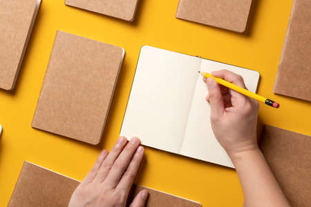 content marketing concept,.top view of hand writing on open notebook align with paper book in pattern on yellow table background. mockup for advertise content online