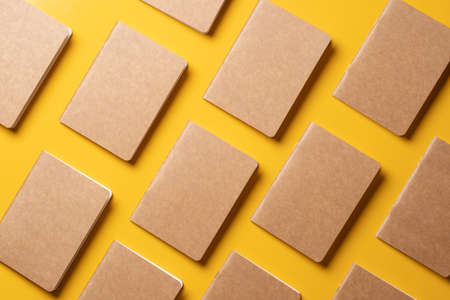creativity content marketing concept,.top view of notebook align in pattern on yellow table background. mockup for advertise content online.unique idea
