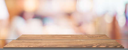 Empty wood table with blur people in coffee shop background bokeh light and leaf foreground,Mockup for display or montage of product,Banner for advertise on online media,business presentation