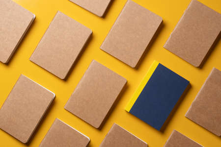 creativity content marketing concept,.top view of blue notebook align in pattern on yellow table background. mockup for advertise content online.unique idea