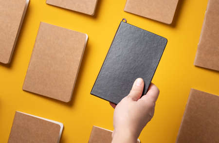 content marketing.hand holding black notebook over brown book on yellow table background.select unique idea