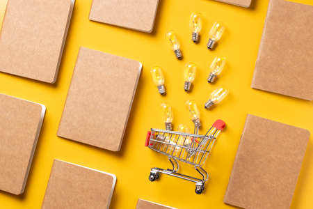 creativity content marketing concept,top view shopping cart with full of light bulbs with paper book alignment in pattern on yellow desk surface.leave space for display your content.