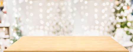 Wood table with Christmas decor in living room blur background with bokeh light,Holiday backdrop,Mockup banner for display of advertise product ,luxury house. Stock Photo