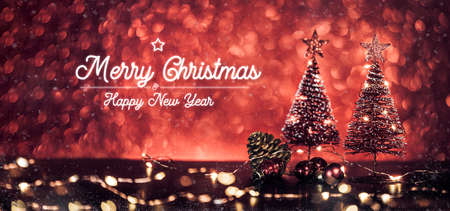 Merry Christmas and happy new year text over xmas tree on red glitter sparkling lights festive bokeh background.holiday greeting card Stock Photo