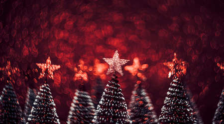 Christmas tree with star on red glitter swirly sparkling lights festive bokeh background.new year holiday greeting card