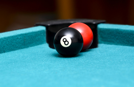 red ball behind the eight ball on pool table Imagens