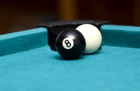 Eight ball and cue ball on pool table Archivio Fotografico