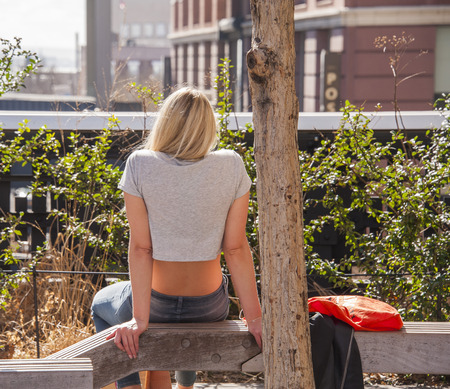 Blonde woman relaxing in High Line Park, New York City