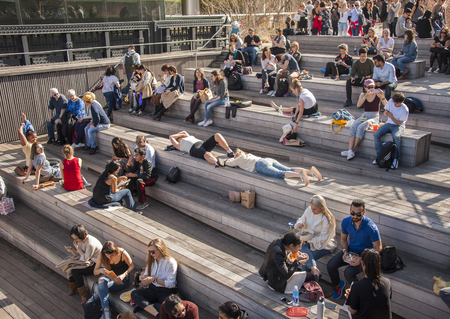 New Yorkers enjoying pleasant weahter in High Line Park Редакционное