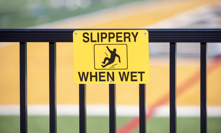 Yellow Slippery When Wet warning sign on hand rail