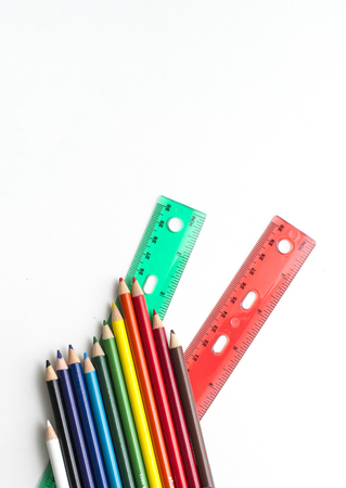 Colored pencils and rulers on white background
