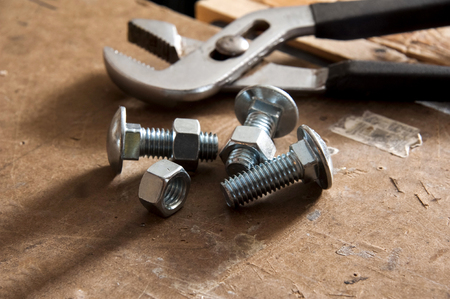 Nuts and bolts on workbench with pliers in background 写真素材