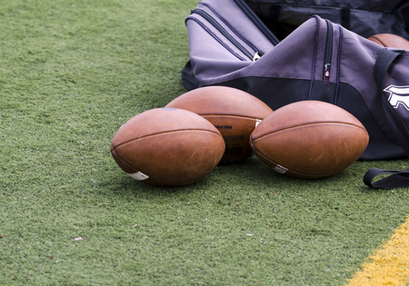 Footballs On The Field With Purple Duffle Bag
