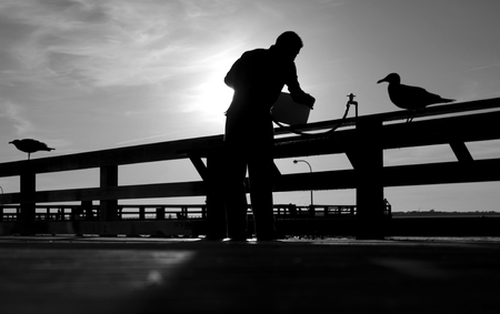 Black And White Photo Of Man On Fishing Pier