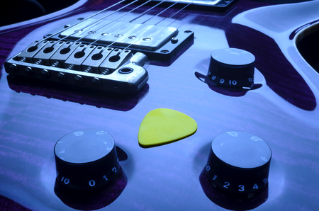 Close Up Of Purple Electric Guitar And Yellow Guitar Pick
