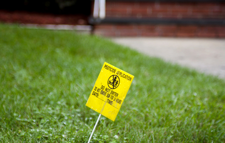 Yellow Pesticide Application Warning Sign On Green Grass