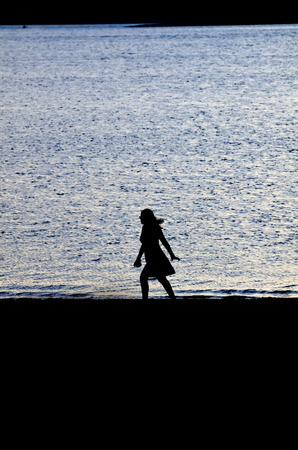 Silhouette Of Woman Walking Along The Shore At Twilight 写真素材