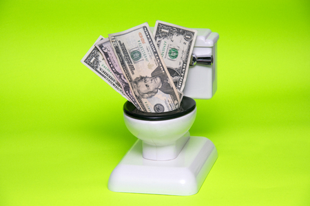 Money Being Flushed Down The Toilet Against Green Background 写真素材
