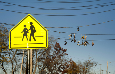 School Crossing Sign With Old Sneakers In Background