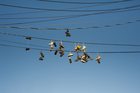 Old Grunge Athletic Footwear Hanging On Telephone Cables