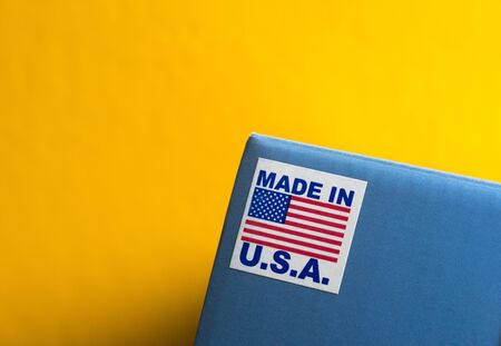 Made In U.S.A. Emblem On Blue Package Against Yellow Background