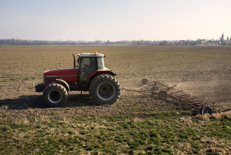 agriculture industrial: Red tractor works on field. Farmer harrows soil clods in rural area. Agriculture industrial motive with plow. Exterior profile countryside scene in spring. Graphic component, partition element.