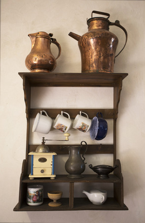 grunge silverware: Old dishes. Historical Cookware. Old hunged on wooden shelf on medieval wall. Antique equipment hanged design, cup, mug, kettle, coffee grinder, small mill, salt cellar and saucepan.