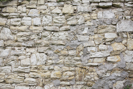 gray texture: Old stone wall texture. Old rock blocks in old medieval brick. Exterior historical country situation with fencing. Village foundation rural background.