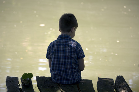 daydream: Dreamy boy sitting on a wooden pier at the pond. Little kid thinks and looks at the pond. Dream positive atmosphere, sunny day. Stock Photo