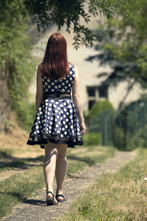 and hiking path: Young woman walking on village way. Woman in spotted dress and red hair. Sunny and positive rural scene with woman walking away from camera.