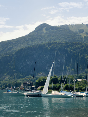 wolfgang: Small harbor in Wolfgang see mountain lake. Anchored yachts, sunny weather. Summer sailing in the Alps. Sport hiking landscape background. Stock Photo