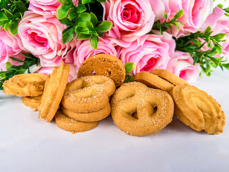 almond cookies and rose on wooden Stock Photo