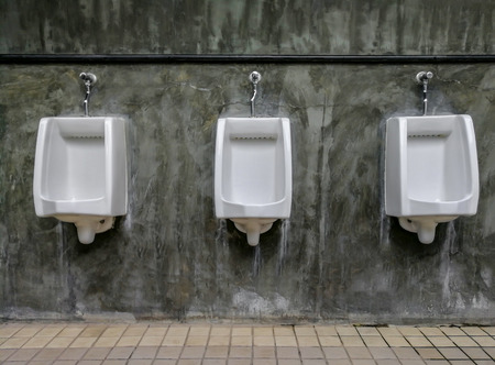 Closeup of three white urinals in mens bathroom design of white ceramic urinals for men in toilet room