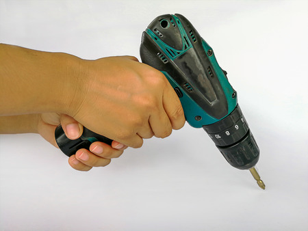 Electric drill holding in hands isolated on the white background