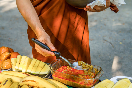 Mans(lama) hand with metal ladle (spoon) and soup in cauldron at background. Camping cooking Stock Photo