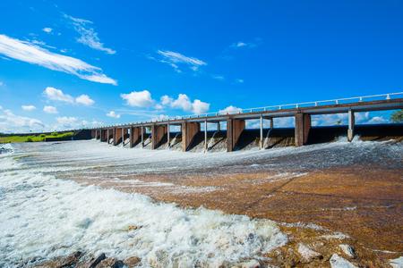 L'acqua del fiume scorre rapidamente sopra una diga di troppo pieno