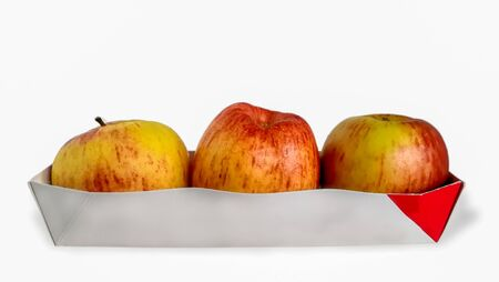 Three red apples on a white background. Juicy apples of red color with yellow specks on a white background. A group of ripe apples on an isolated background