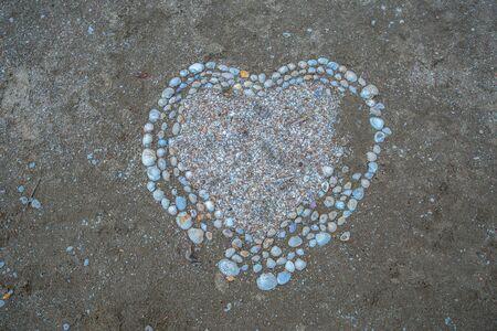 Heart shape maked of sea shells on sand
