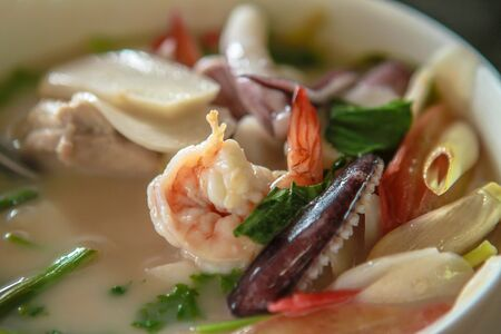 Macro shot of hot chili tom yum or tom yam with squid, shrimp, red peppers, lime juice, galangal, fish sauce, lemongrass. Traditional red sour thai soup cooked with fragrant spices closeup Stock Photo