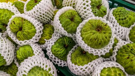 stacks of sugar apple at the traditional marketplace in Thailand